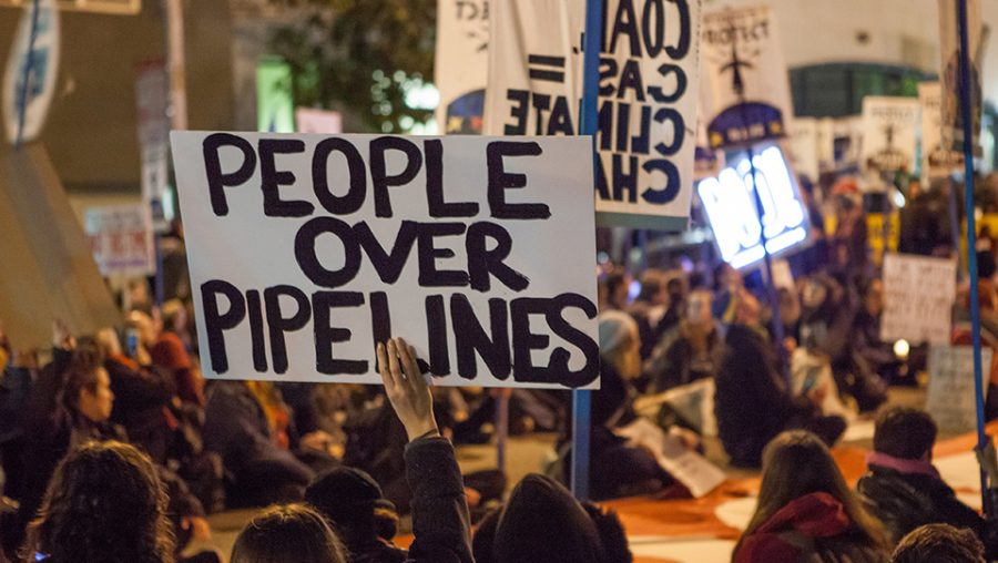 Protesters against the Dakota Access Pipeline and Keystone XL Pipeline hold a sit-in in the street next to the San Francisco Federal Building. (Source: Wikimedia Commons)